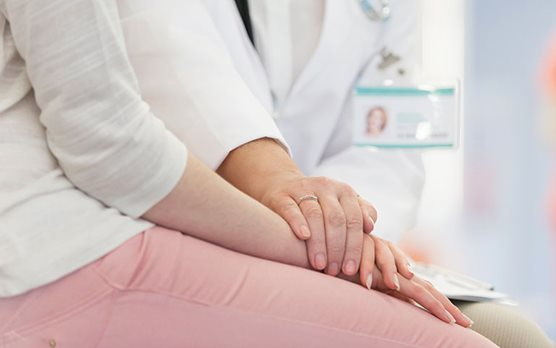 Doctor putting her hand on a patient